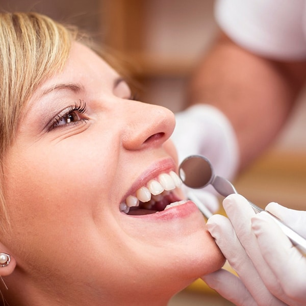 Woman in dental chair smiling with dentist and dental tool