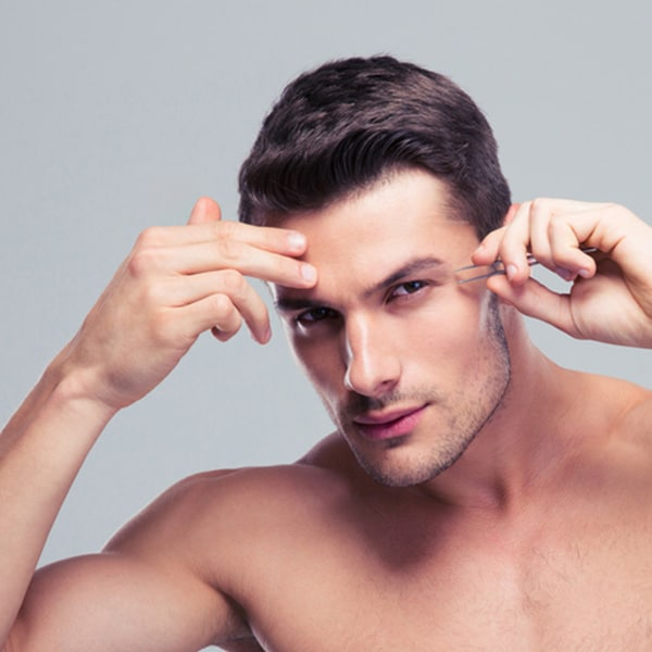 Handsome man removing eyebrow hairs with tweezing over gray background and looking at camera