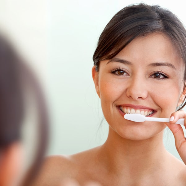 Woman looking in to the mirror brushing teeth