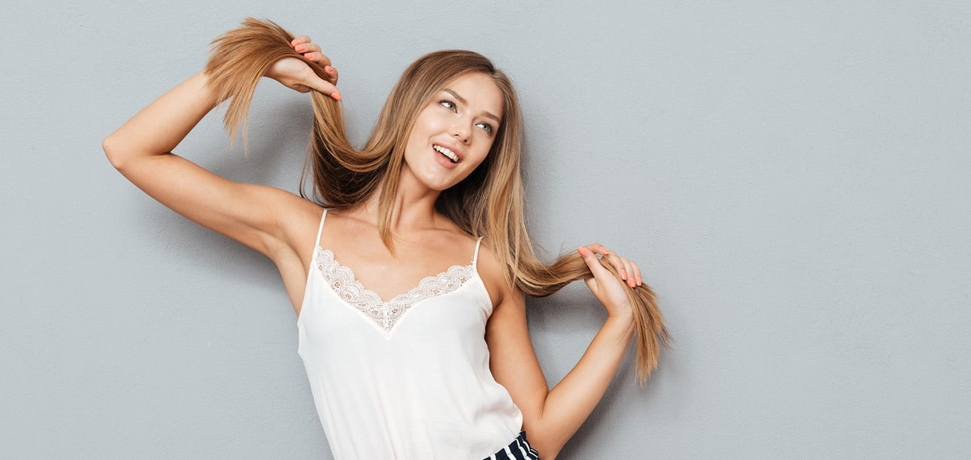 woman looking away from camera smiling and holding hair